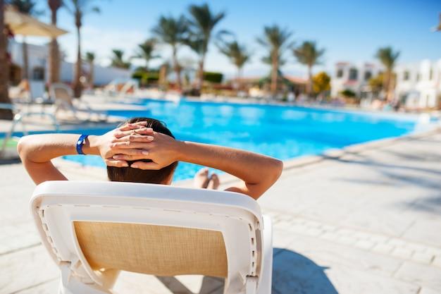 Femme allongée sur une chaise longue au bord de la piscine bleue