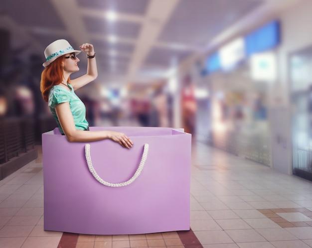 Femme allongée dans le sac à provisions tenant son chapeau dans le centre commercial