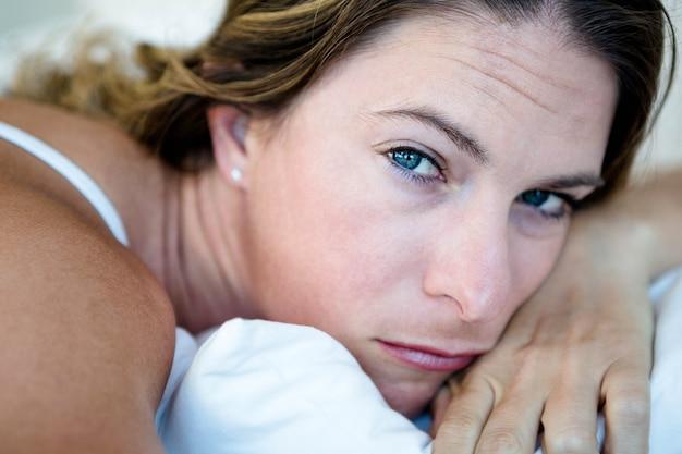 Femme allongée dans son lit, la tête appuyée sur ses mains, l'air triste