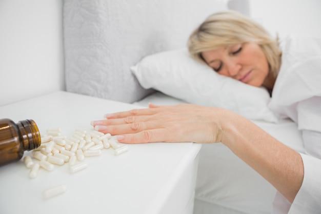 Femme allongée immobile à côté des pilules