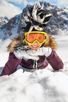 Femme allongée sur la neige à la montagne en journée ensoleillée avec ciel bleu et vue sur le gros rocher en arrière-plan