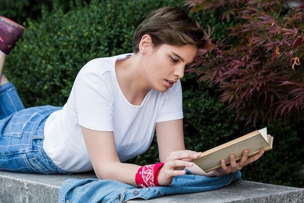 Femme allongée sur le parapet du parc avec livre