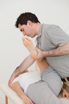 Femme allongée pendant qu'un physio bouge sa jambe