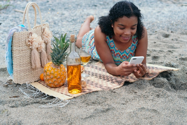 Femme allongée sur la plage vérifiant son téléphone portable