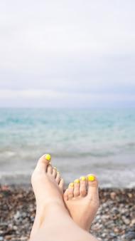 Femme allongée près de l'eau. jambes de femme près de la mer bleue - photo verticale