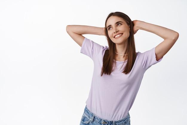 Femme allongée et rêvant de vacances, tenant les mains derrière la tête et regardant de côté souriant sur blanc