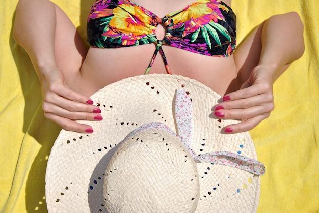 Femme allongée sur sa serviette avec un chapeau sur la plage