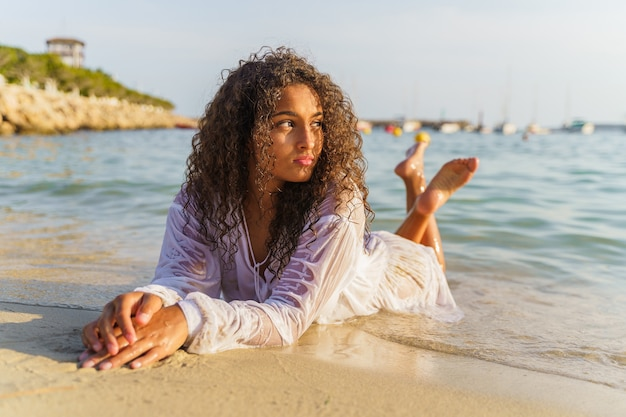 Femme allongée sur le sable et regardant l'horizon