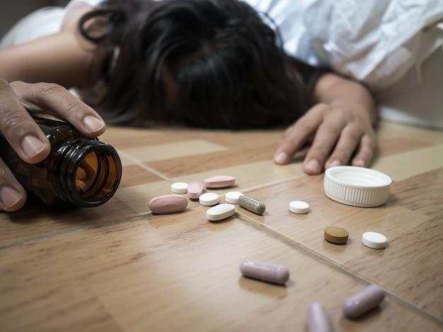 Femme allongée sur le sol après une overdose de pilules à la maison