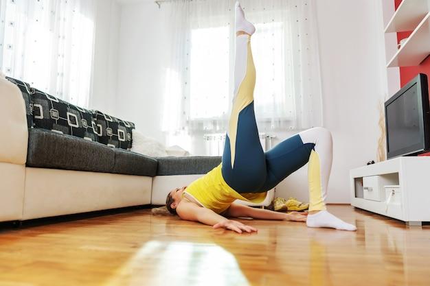Femme allongée sur le sol et faire des exercices de remise en forme pendant le verrouillage.