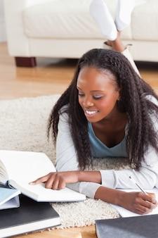 Femme allongée sur le sol travaillant sur une critique de livre