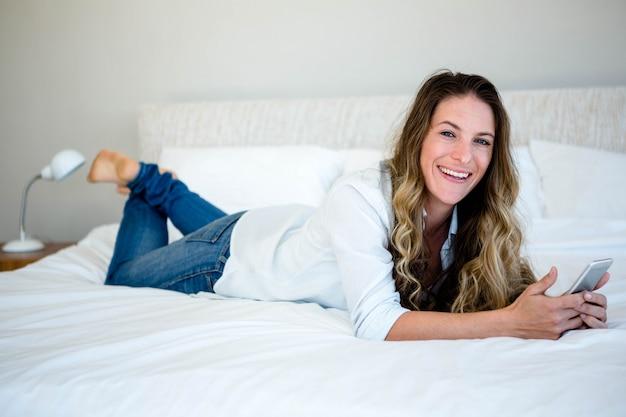 Femme allongée sur son lit sur son téléphone portable souriant