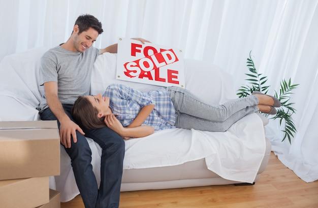 Femme allongée sur son mari dans le canapé dans leur nouvelle maison
