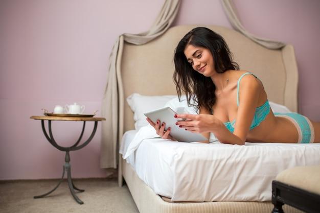 Femme allongée et tenant la tablette.