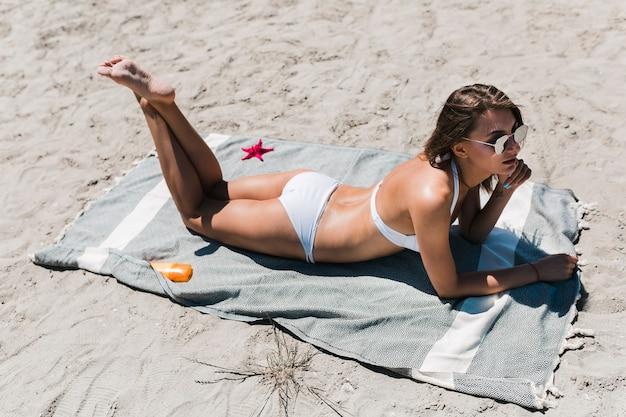 Femme allongée sur le ventre sur la plage