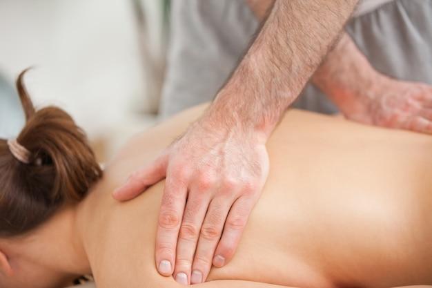 Femme allongée sur le ventre tout en étant massée sur le dos