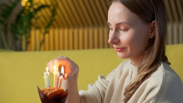 Femme allume une bougie sur un délicieux gâteau