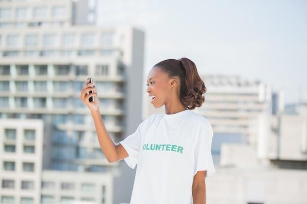 Femme altruiste joyeuse en regardant son téléphone portable