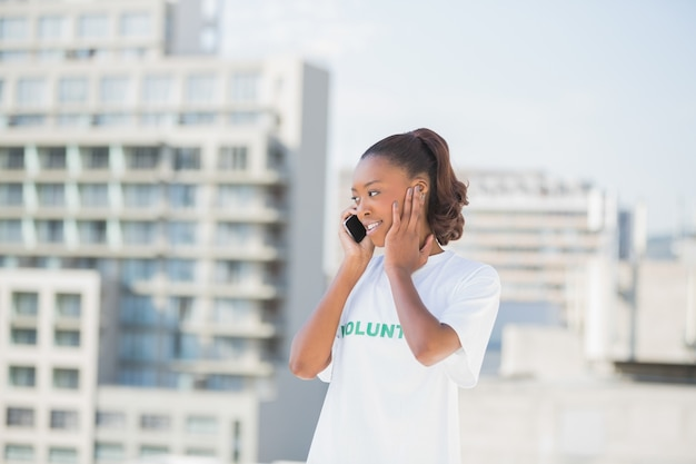 Femme altruiste joyeuse sur le téléphone couvrant son oreille