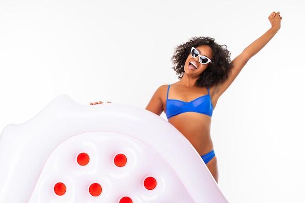 Femme américaine africaine, sur, fond blanc, à, matelas pneumatique, sourire