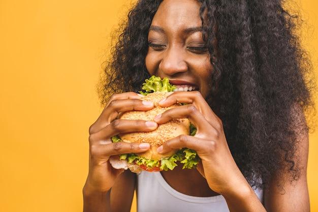 Femme américaine africaine, manger, hamburger
