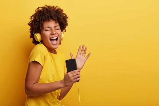 Femme américaine africaine, porter, t-shirt jaune, et, écouteurs