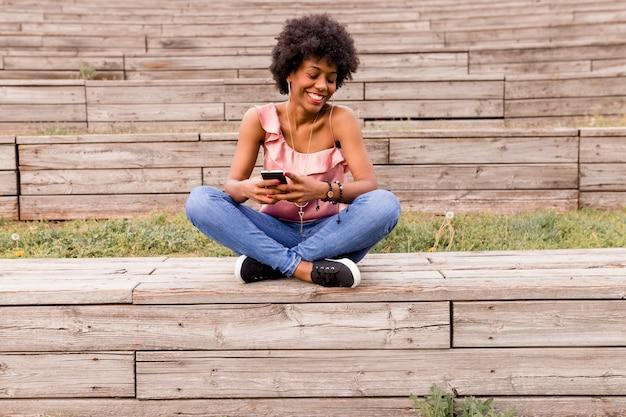 Femme américaine afro à l'aide de téléphone portable à l'extérieur