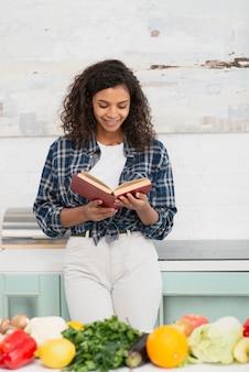 Femme américaine afro vue de face, lisant un livre