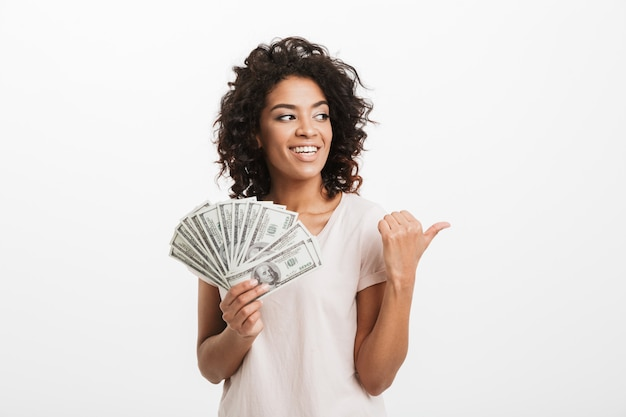 Femme américaine chanceuse aux cheveux bruns bouclés holding fan de billets en dollars d'argent et faisant des gestes du doigt de côté sur copyspace, isolé sur mur blanc