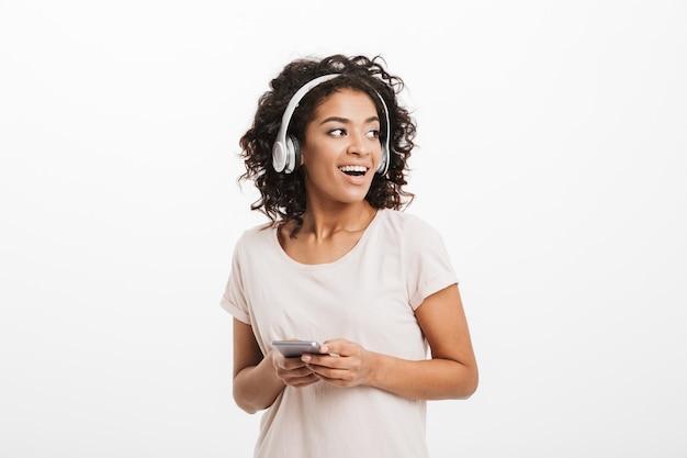 Femme américaine moderne avec coiffure afro et grand sourire à la recherche de côté tout en écoutant de la musique via des écouteurs sans fil et un téléphone portable, isolé sur un mur blanc