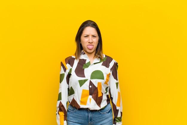 Femme d'amérique latine se sentant dégoûté et irrité, tirant la langue, n'aimant pas quelque chose de méchant et dégueu isolé contre le mur jaune