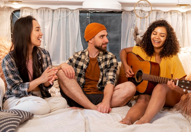 Femme et amis jouant de la guitare