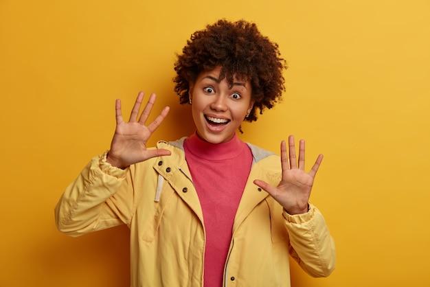 Une femme amusée et ludique avec des cheveux afro montre des paumes à la caméra, joue avec un petit enfant, se trompe et sourit joyeusement, a une humeur optimiste