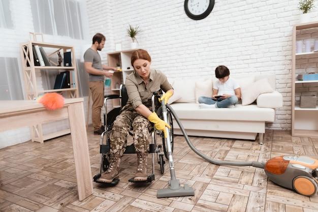 Une femme ancien combattant en fauteuil roulant nettoie la maison.