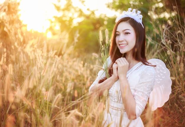 Femme ange dans un champ d'herbe avec la lumière du soleil