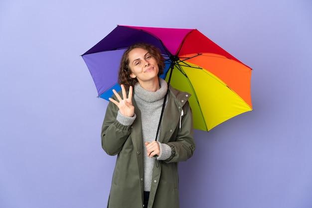 Femme anglaise tenant un parapluie sur fond violet heureux et en comptant quatre avec les doigts