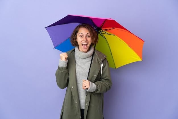 Femme anglaise tenant un parapluie isolé célébrant une victoire en position de gagnant
