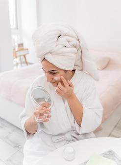 Femme à angle élevé, appliquer la crème pour le visage