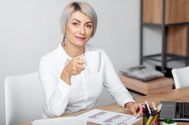 Femme, angle élevé, bureau, boire café