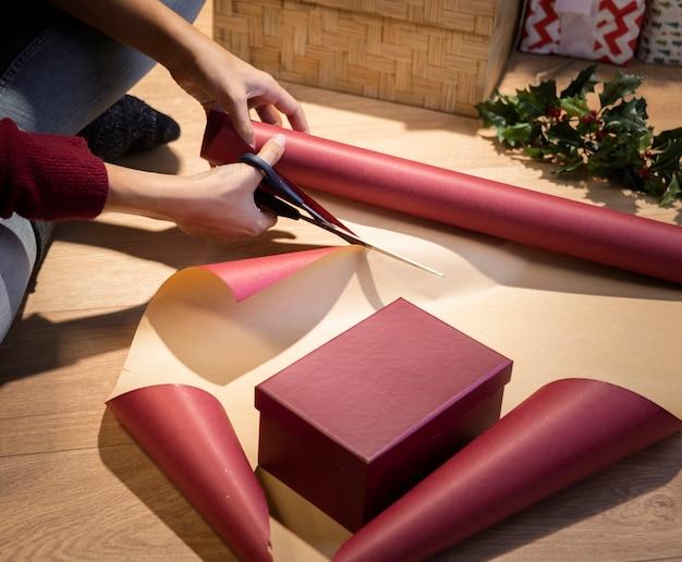 Femme à angle élevé coupant du papier pour emballer des cadeaux