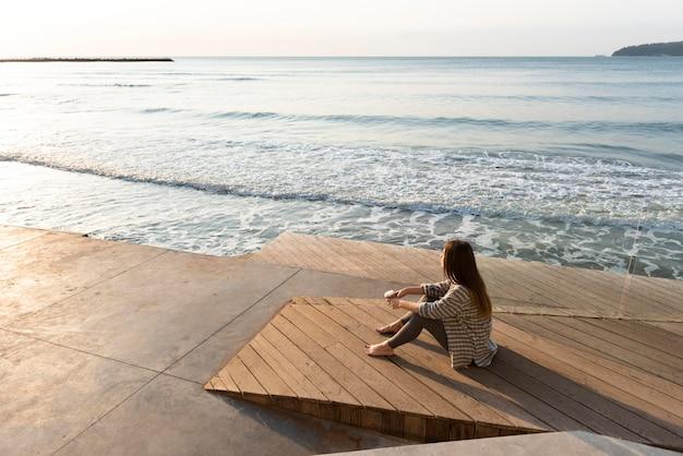 Femme à angle élevé de détente à côté de la plage