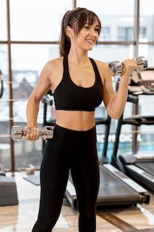 Femme à angle élevé exerçant avec des poids