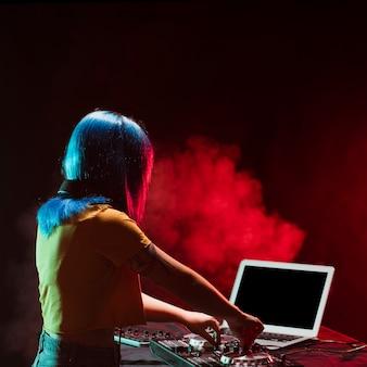 Femme à angle élevé mixant une console audio