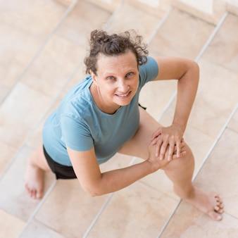 Femme à angle élevé qui s'étend des jambes