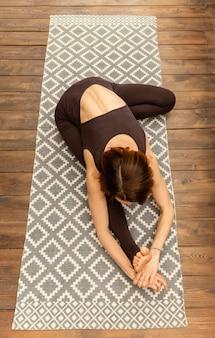 Femme à angle élevé qui s'étend sur un tapis de yoga