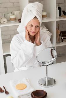 Femme à angle élevé regardant dans le miroir