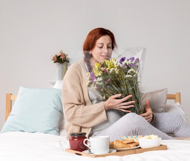 Femme, angle élevé, sentir, fleurs, bouquet