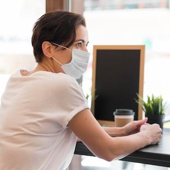 Femme à angle élevé à la terrasse portant un masque
