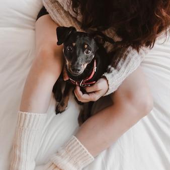 Femme anonyme avec chien sur lit