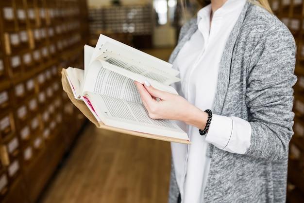 Femme anonyme feuilletant des pages de livre